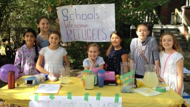 Students sell lemonade to make enough money to bring a Syrian family to Canada on a warm day this past October.