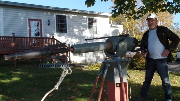 Vaughan George stands beside the harpoon gun from his father's whaling vessel. It's now mounted on his front lawn. George still fires the gun off every New Year's Eve at midnight.