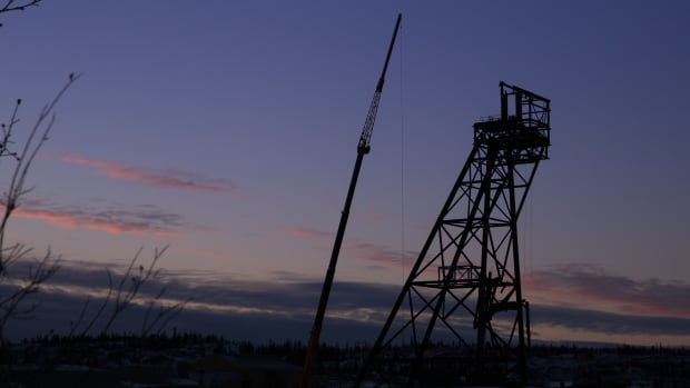 The partially deconstructed headframe of Giant Mine sits in the evening light, flanked by a crane preparing to dismantle it.