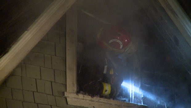 A Captain with Vancouver Fire and Rescue peers out a top floor window to see if flames are still creeping through the wall, Thursday night.