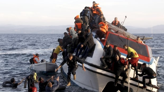 Refugees, most of them Syrians, struggle to leave a half-sunken catamaran carrying around 150 people as it arrives on the Greek island of Lesbos, after the Aegean Sea from Turkey on Friday.