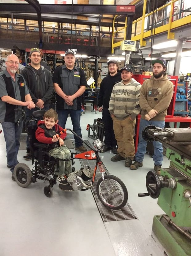 Rob Gilchrist and his students at Saskatchewan Polytechnic stand with the Henry Davidson motorcycle they fashioned for Henry Craig. (Submitted by Rob Gilchrist)
