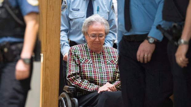 Former Quebec lieutenant governor Lise Thibault is escorted by agents, leaving the courtroom after receiving an 18-month prison sentence at the courthouse in Quebec City.