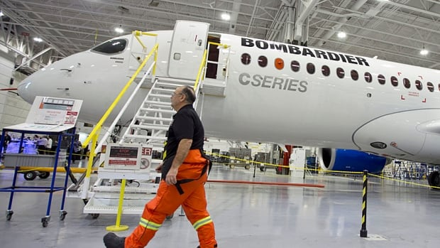 A Bombardier worker walks past the CS300 Aircraft in the hangar prior to its test flight in Mirabel, Que., last year.