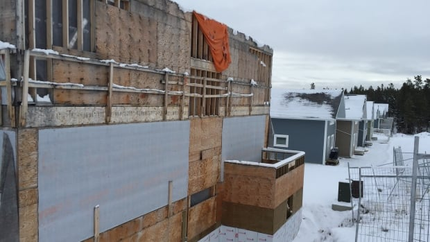Construction on the apartment building in Whitehorse's Falcon Ridge neighbourhood was halted by court order in 2013. Homeowners in an adjacent condo complex say the shell will be torn down by summer.