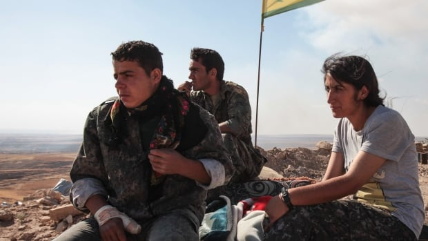 Members of the Kurdish People's Protection Units, or YPG, stand guard near a check point in the outskirts of the destroyed Syrian town of Kobani in this June 20 photo. A Canadian man arrested in Iraq reportedly had volunteered with the YPG.