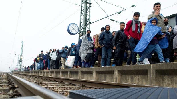 Migrants make their way to board a train to Duesseldorf, Germany in Passau, near the Austrian border, southern Germany on Tuesday.
