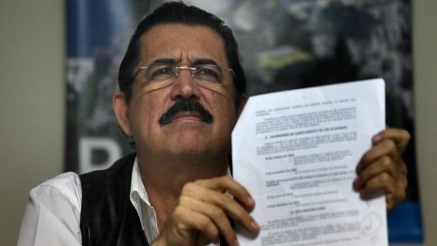 Honduras' ousted President Manuel Zelaya holds up a document during a news conference inside the Brazilian embassy in Tegucigalpa November 4, 2009. Zelaya  called on Washington to state clearly whether it supported his return to power or the de facto government that ousted him.