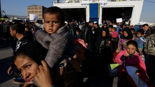 Refugees and migrants arrive from the island of Lesbos to the port of Piraeus on Friday. About 25,000 refugees and other migrants are heading to the Greek mainland from the eastern Aegean islands after the country's seamen's union called off rolling, 48-hour ferry strikes.