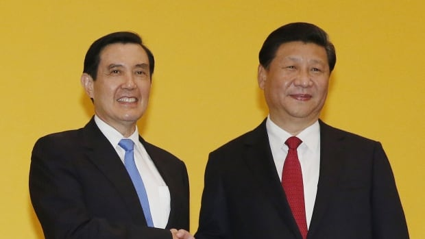 Chinese President Xi Jinping right shakes hands with Taiwanese President Ma Ying-jeou during a summit in Singapore