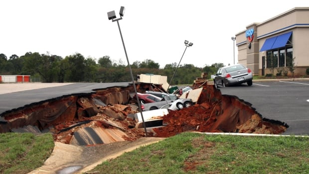 This photo shows vehicles after a cave-in of a parking lot in Meridian, Miss., on Sunday, Nov. 8, 2015. Experts are to begin work Monday seeking to determine the cause of the Saturday collapse, authorities said.