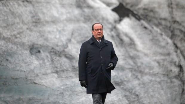 French President Francois Hollande walks on the Solheimajokull Glacier, where the ice has receded by more than one kilometre, during a visit in Iceland in October to experience firsthand the damage caused by global warming, ahead of the UN talks on climate change in Paris.