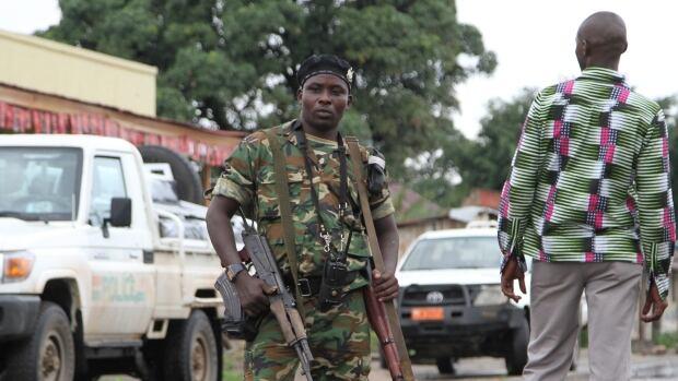 A Burundian  soldier with his gun and rocket launcher guard a deserted street in Bujumbura, Burundi, Sunday, Nov. 8, 2015.