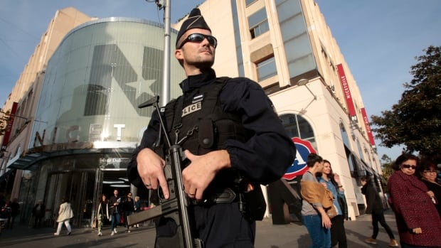 A French policeman stands guard outside a commercial centre in Nice, France, the day after a series of deadly attacks in Paris. France and other countries have beefed-up security after Friday night's shootings and bombings.