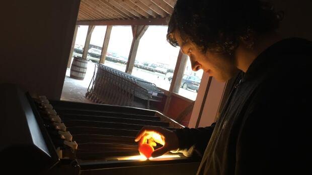 Samuel Martineau Dubois checks a local egg in the egg grading station to ensure quality at Farmer Robert's in Whitehorse
