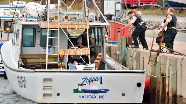 Fisheries officers are shown getting ready to board the Zappa.