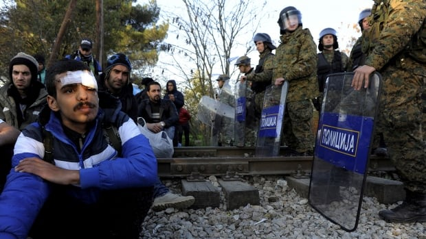 Migrants sit on the Greek side of the border with Macedonia as Macedonian policemen stand guard near the Macedonian town of Gevgelija, November 19, 2015. Balkan countries have begun filtering the flow of migrants to Europe, granting passage to those fleeing conflict in the Middle East and Afghanistan but turning back others from Africa and Asia, the United Nations and Reuters witnesses said on Thursday. Picture taken from the Greek side of the Greek-Macedonian border near the Greek village of Idomeni.
