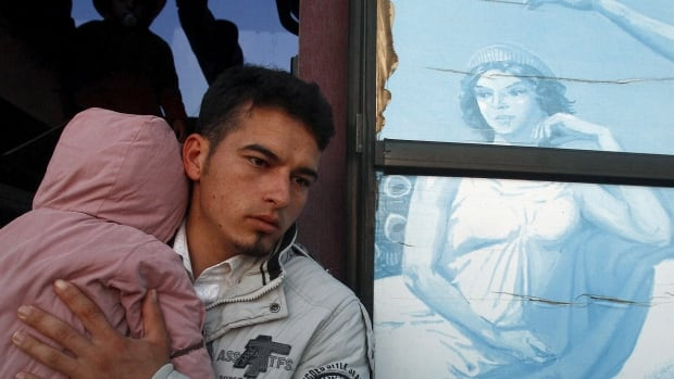 A migrant holding a baby steps off a bus with depictions of ancient Greek gods as he arrives at a camp before crossing Greece's border with Macedonia near the Greek village of Idomeni. Fears about Canada's Syrian immigrants are misplaced, and a more important worry is the economic inclusion of the next generation.