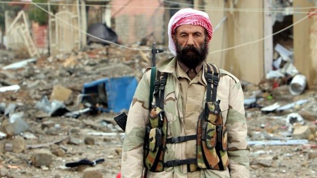 A member of the Kurdish peshmerga forces poses for a photograph in the town of Sinjar, Iraq November 16, 2015. Under the federal government's new multi channel ISIS mission soldiers like these would be supplied small arms by Canada.