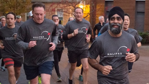 Canadian Defence Minister Harjit Singh Sajjan, right, is followed by former defence minister Peter MacKay as he leads a five-kilometre run on the third day of the Halifax International Security Forum in Halifax.