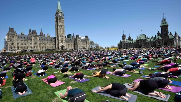 People take part in a yoga session on Parliament Hill in Ottawa earlier this year. A free yoga class at the University of Ottawa was cancelled partly because of cultural concerns, but some members of Ottawa's Hindu community say they don't feel offended by it.