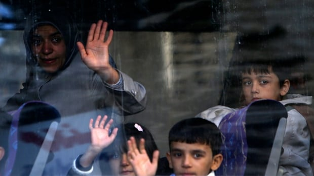 A Syrian refugee family waves to relatives after boarding a bus in Beirut. There are 1.1 million Syrians living in Lebanon registered with the UN's refugee agency, but the Canadian government is taking in just 25,000 — from Lebanon, Jordan and Turkey — by year's end.
