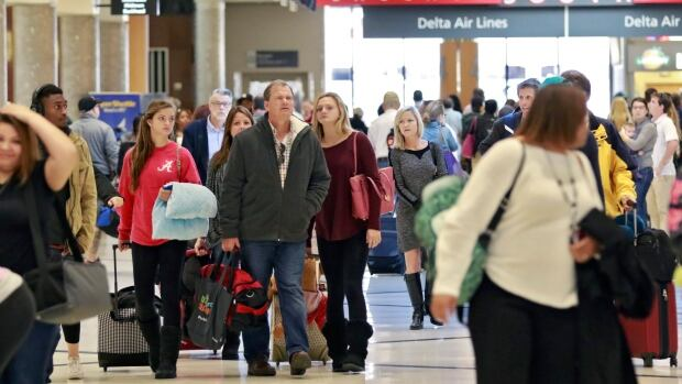 Travellers walk toward baggage claim at Hartsfield-Jackson Atlanta International Airport on Friday, Nov. 20, 2015, in Atlanta. The U.S. State Department is warning Americans of possible risks of travel because of increased threats from militant groups.