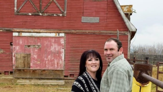 Petition founder Shandele Battle stand with her husband, Ted, in front of their farm in Delia, Alta.