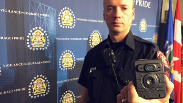 A Calgary Police officer shows a body-worn camera in a file photo. Edmonton police have shelved a plan to have officers wear similar devices due to the cost of the program.