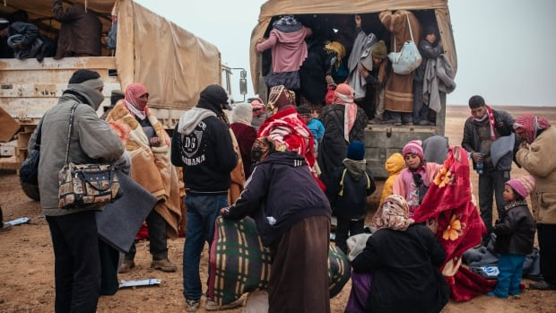 Refugees collect supplies at the Hadarat border crossing between Jordan and Syria. Refugees and agencies can now keep track of service points like this using a new app developed by the Vancouver organization, Peace Geeks.