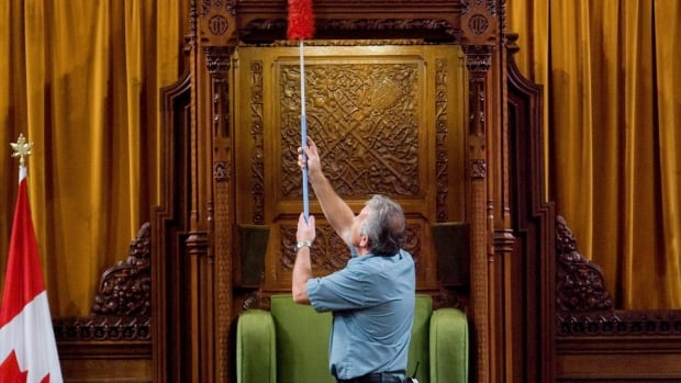 A worker dusts the Speaker's chair in the House of Commons. A new Speaker will be elected on Thursday, the first day of the new parliamentary session.
