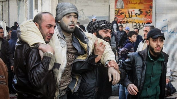 Syrian citizens help an injured man after airstrikes believed to be carried out by Russian warplanes hit the centre of Ariha, a town in the northwestern province of Idlib, Syria, on Sunday, Nov. 29, 2015. This photo was provided by the Syrian anti-government activist group Ariha Today, and has been authenticated based on its contents and other Associated Press reporting.