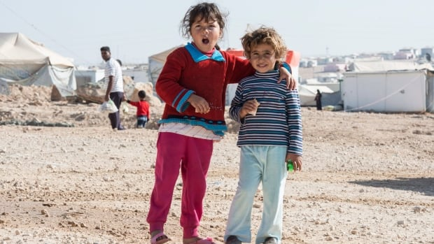Two young Syrian refugee girls smile for the camera in the Zaatari Refugee Camp, near the city of Mafraq, Jordan, on Sunday, Nov. 29, 2015.
