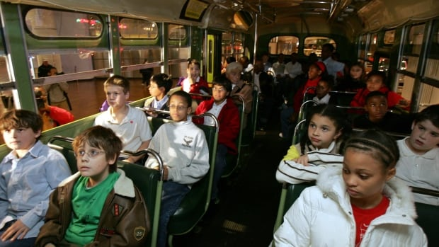 Students sit next to each other on the actual bus where Rosa Parks, a black woman, refused to give up her seat to a white man 50 years ago in Alabama, during their school visit to Henry Ford Museum in Dearborn, Michigan.