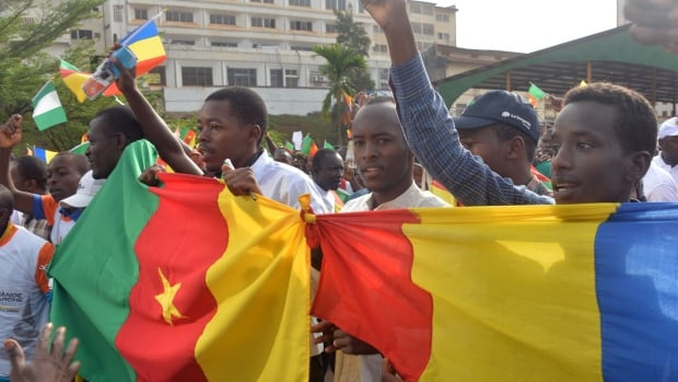 People wave Cameroon's national flag in a demonstration against Islamist group Boko Haram on Feb. 28 in downtown Yaounde. The army said Wednesday it has killed at least 100 militants and freed 900 hostages.