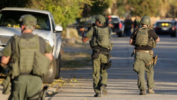 Law enforcement officers search for suspects in the mass shooting at a social services centre in San Bernardino, Calif. There are believed to have been three attackers, two of whom have been shot and killed by police. A third suspect is in custody.