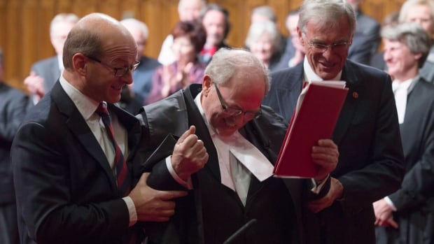 The new Senate Speaker George Furey is escorted to the Speakers throne by Senator James Cowan and Senator Claude Carignan after being sworn in during a ceremony in the Senate chamber in Ottawa, Thursday Dec. 3, 2015.