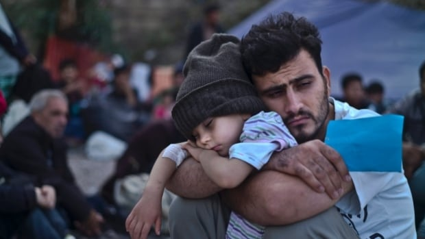 A Syrian refugee child sleeps in his father's arms while waiting at a resting point to board a bus, after arriving on a dinghy from the Turkish coast to the northeastern Greek island of Lesbos.
