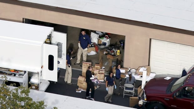 FBI investigators sort through contents of the garage of the home in Redlands, Calif., rented by the husband and wife who opened fire at a holiday party in San Bernardino, killing 14 people and wounding 21.