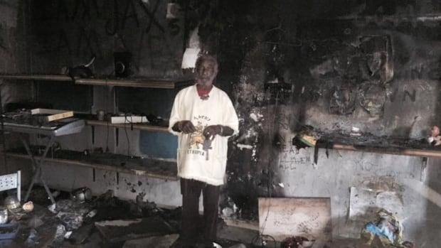 "Lee ""Scratch"" Perry stands in his burned down studio, in Switzerland."