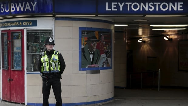 A police officer patrols outside Leytonstone Underground station in east London on Sunday following an attack at the station the previous night.