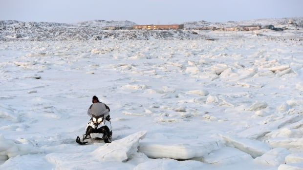 A snowmobiler makes his way through the ice heaves in Frobisher Bay in Iqaluit, Nunavut, on December 10, 2014. If climate changes goes unchecked in the Arctic, an Environment Canada researcher estimates the ice season could be seven weeks shorter and a nearly ice-free summer could develop sometime between 2020 and 2040.