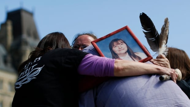 A photograph of Terrie Ann Dauphinais is seen as participants hug after singing a song during a24-Hour Sacred Gathering of Drums protest calling for an inquiry into missing and murdered indigenous women, on Parliament Hill in Ottawa in May 2014. Dauphinais was found murdered in her Calgary home on April 29, 2002 and the case remains unsolved.