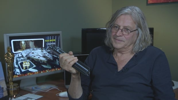 Oscar-winning set decorator, production designer and filmmaker Roger Christian holds the iconic lightsaber handle he created for Star Wars.