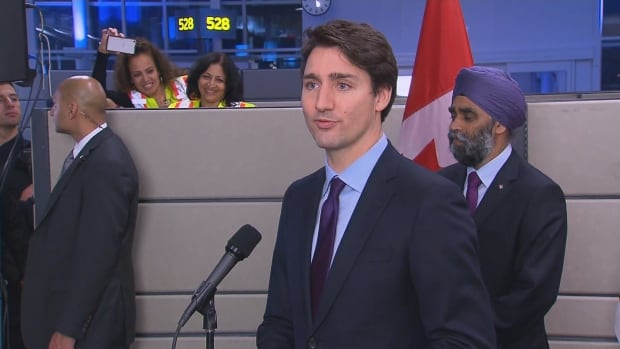 Prime Minister Justin Trudeau addresses staff and volunteers at Toronto's Pearson International Airport before greeting Syrian refugees who arrived on a government-sponsored aircraft.