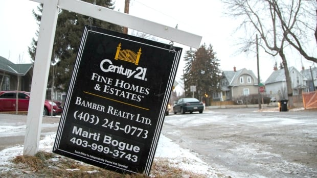 A leaning for-sale sign advertises a luxury home for sale in Calgary.
