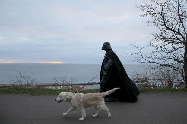 Darth Mykolaiovych Vader walks his golden retriever in Odessa in December