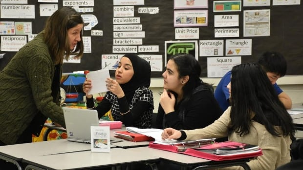 Teacher Sarah Lees helps students with a problem in her Level 3 English class at Queen Elizabeth School in Edmonton.