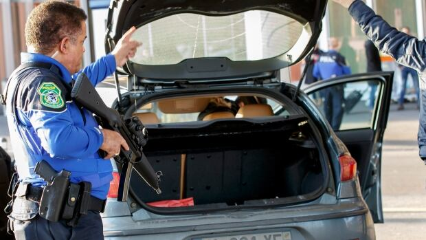 Swiss police officers check a car at the Geneva airport during a high level of alert on Thursday, after a man said to be a friend of a suspect in the Paris attacks fled from a late-night police checkpoint and into France.