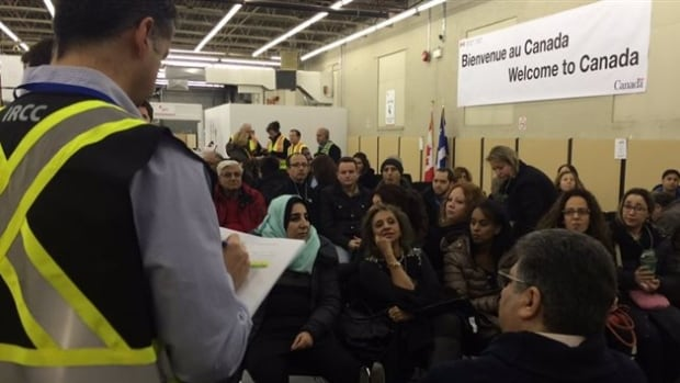 Newly arrived Syrian refugees wait to be processed at a special facility at Montreal's Trudeau airport.